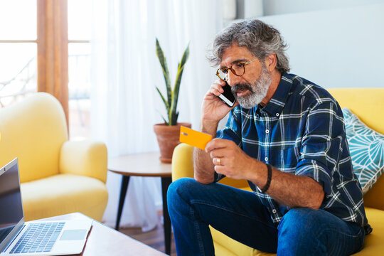 Adult man talking by phone at home office