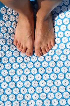 Unrecognizable person standing on spiky massage mat