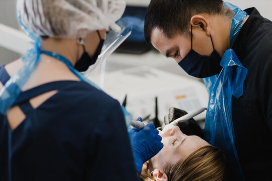 Male and female dentists healing woman