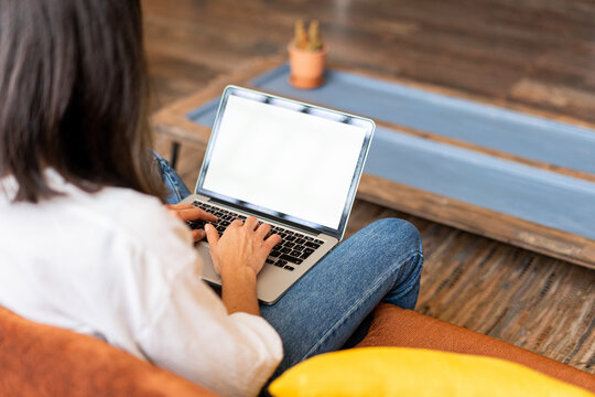 Back view of focused female freelancer working on laptop from home office