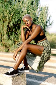 Trendy black woman resting on barrier