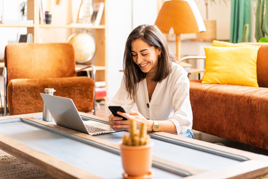Young woman freelancer working on laptop and using smartphone from home office