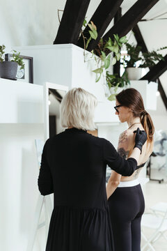 Tattoo artist and client in a tattoo studio.