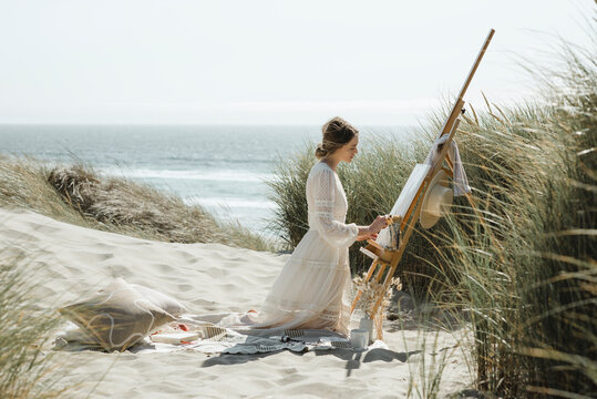 Young woman painting at the coast in the dunes