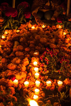 Marigolds and Candles form a Cross on a Grave