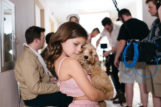 Girl holding a puppy on a film set