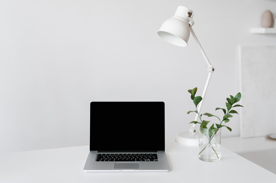 Minimalistic workplace with laptop and lamp