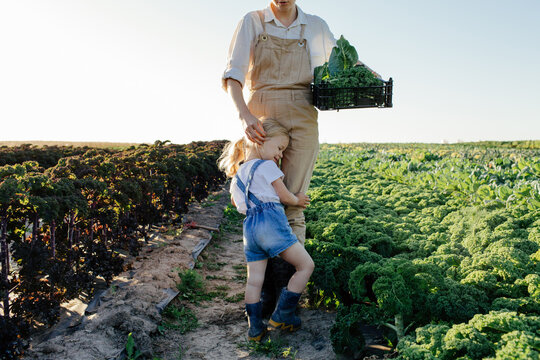 Female farmer with child harvesting greens in field