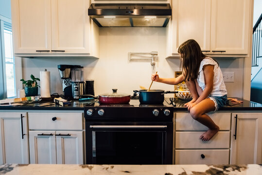 Girl sitting on kitchen counter helping cook dinner.