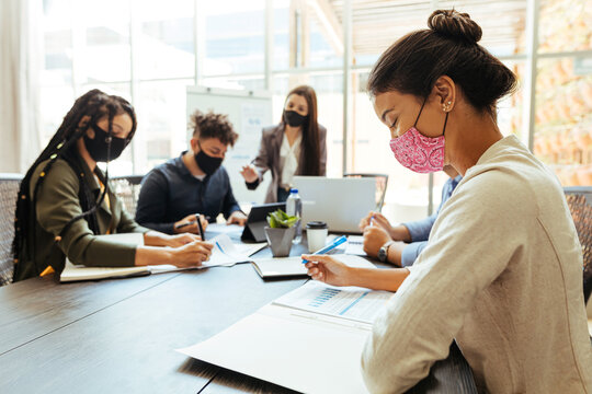 Business team wearing protective masks while meeting in the office during the COVID-19 epidemic