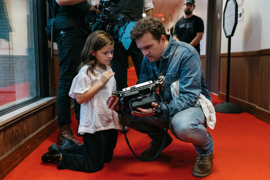 Director and young girl reviewing video monitor