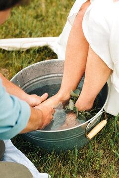 groom washing feet of bride outdoors