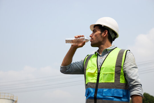 The young engineer drinks water to quench his thirst.