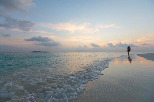 Man running barefeet on a Maldivian beach