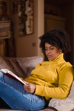 Black woman reading a book on the sofa.