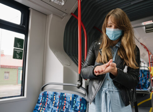 Woman In Bus Wearing Surgical Mask with Hand Sanitizer.