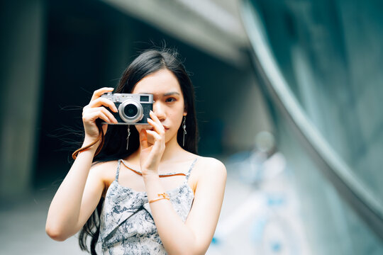 Portrait of young Asian woman using camera