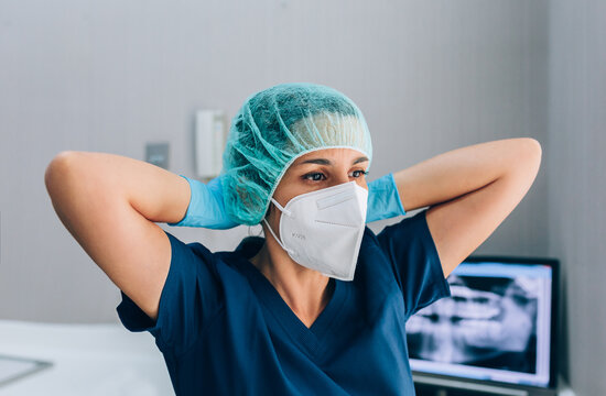 Dental surgeon woman wearing mask and cap while looking away wit