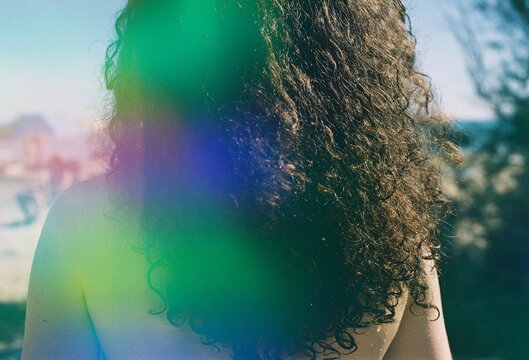 A back portrait of a curly woman on a sunny beach