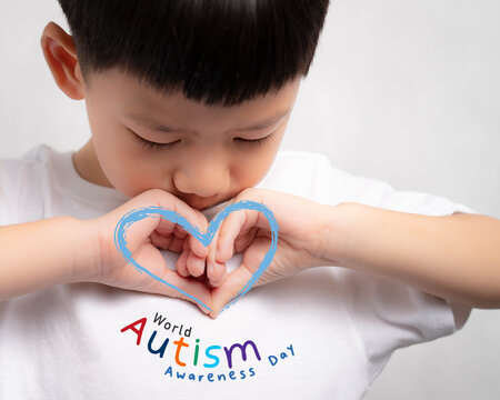 """A little Autistic boy doing heart shape hand gesture with graphic word """"World Autism Awareness Day"""" and blue heart. ASD, Autistic, Charity, Understand, Light it up blue, Caring, love, Acceptance."""