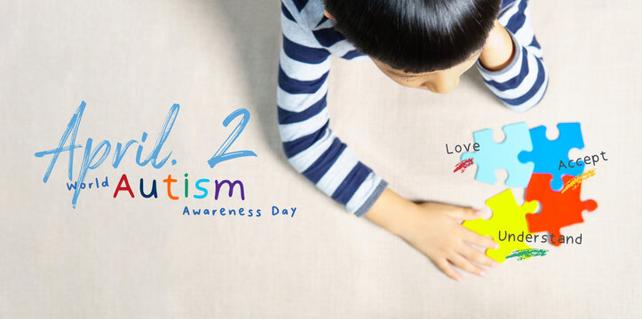 April 2 - World autism awareness day heading. A little Autistic boy staring and playing at colorful ASD symbol puzzles with graphic wording Love, Accept, Understand overlay on it. Mental, Top view.