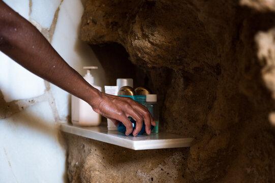 Woman taking soap from shelf in bathroom
