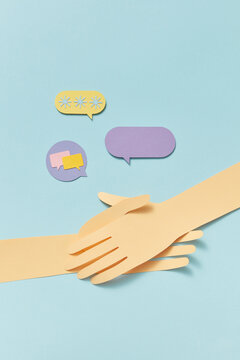 Two crossing papercraft hands with talk cloud icons.