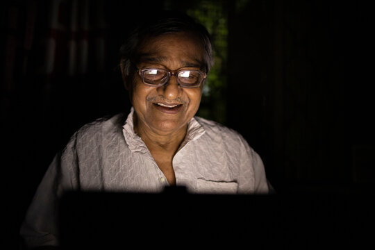 Senior Indian citizen watching movie in a tab
