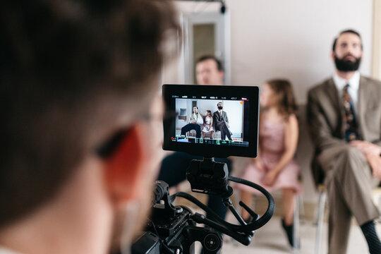 Cameraman watches three actors perform on his camera screen