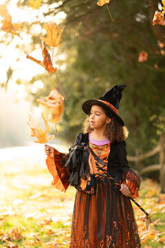 Girl in witch costume catches falling leaf