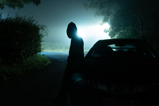 Silhouette of a man back to camera, leaning on a car, at night