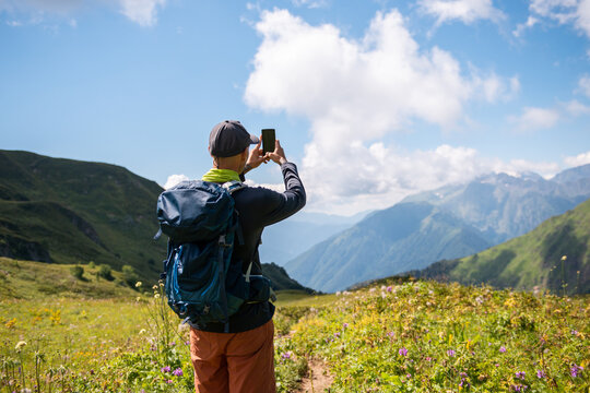 Male hiker taking photo by smartphone