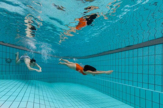 TA couple friends dive underwater in a residential pool in Singapore