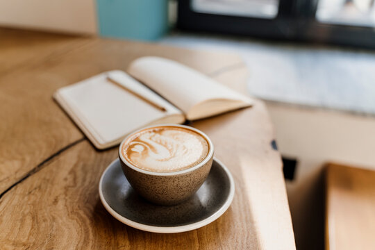 Coffe latte with latte art an notebook on top of table