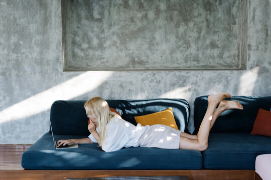 Thoughtful woman using laptop on couch