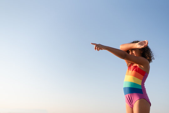Girl in rainbow swimsuit against blue sky pointing
