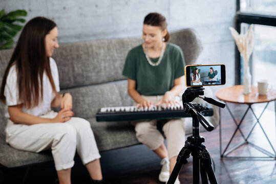 Woman teaching friend to play synthesizer at home