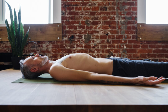 Relaxed middle aged man meditating in Savasana pose