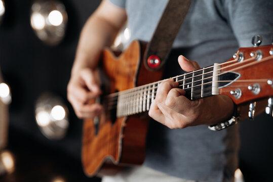 Crop man playing guitar in studio
