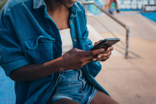 African American woman browsing on her mobile phone, sitting in the skate park