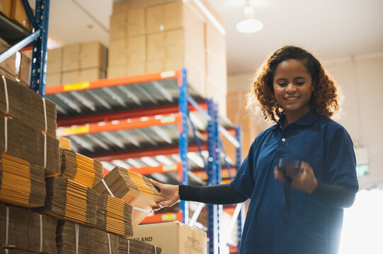 Portrait of African American worker in warehouse, International export business concept, occupation industrial in factory storage, warehouse worker using bar code scanner to analyze newly arrived good