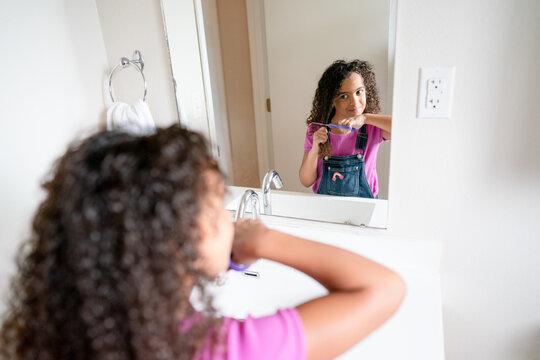 Girl cuts off long curly hair in bathroom mirror