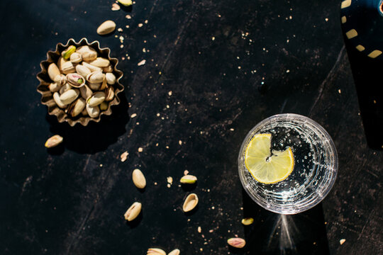 Lemon slice in water glass and pistachio nuts on table
