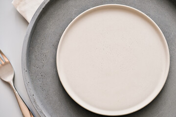 empty grey plates on a table with fork and knife. spring menu concept. trendy nordic minimal style tableware. restaurant menu mock up, scandinavian tableware design, top view