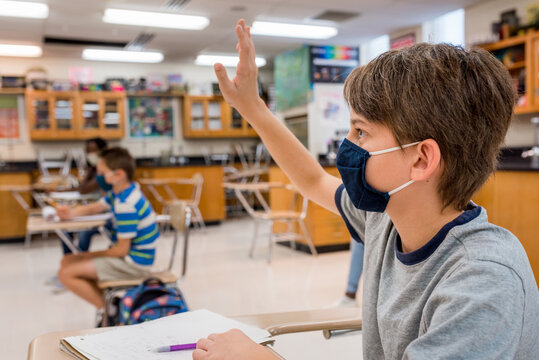 Close up of a boy raising hand in a science class