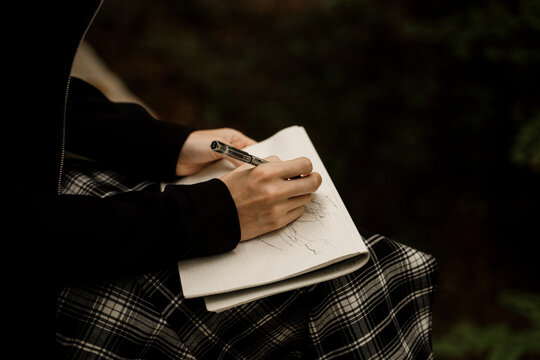 close up of Young woman sitting drawing in notebook in forest during autumn