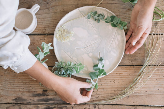 Woman decorating a plate with herb twigs