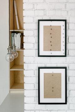 Frames on a brick white wall next to a shelf and light bulbs