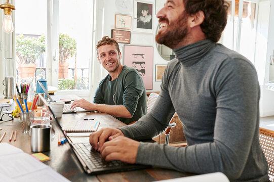 Smiling designers working on laptops