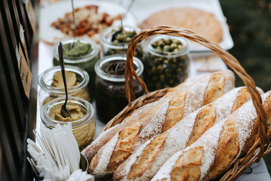Outdoor table with french baguettes in a basket, olives and other spreads